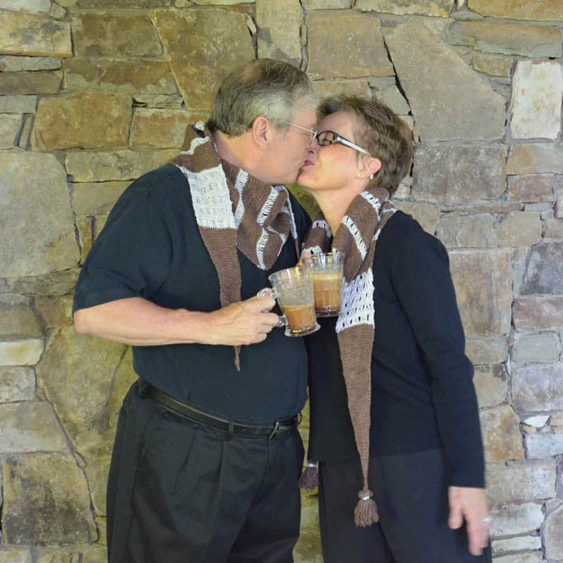 mom and dad sharing a kiss in their bicerin shawls with bicerins to drink