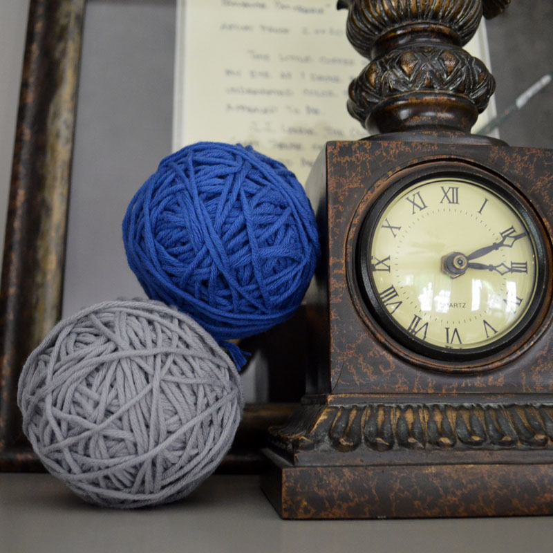 yarn balls next to clock