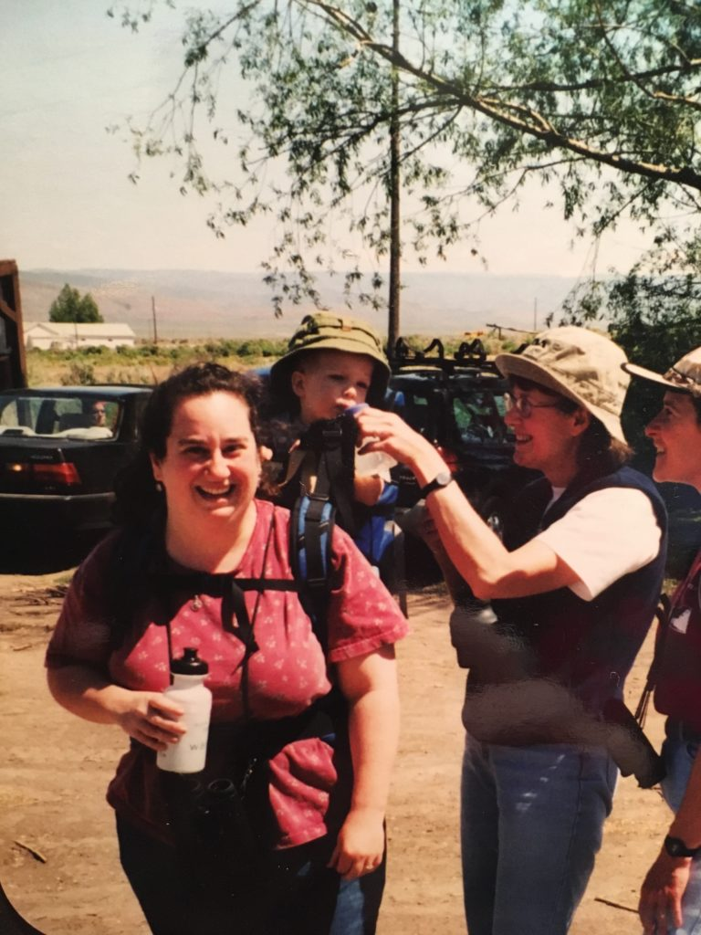 Theressa and her 1 year old son in 2002 on a trip to the Malheur National Wildlife Refuge. A grad school buddy is helping Sam get a drink of water.
